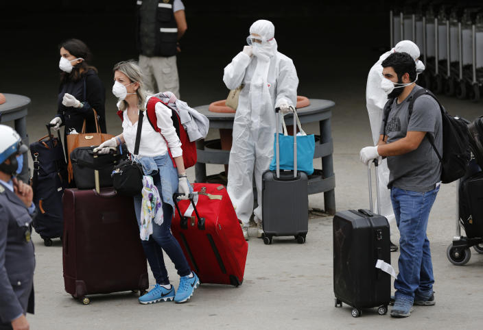 Lebanese passengers who were stuck in Saudi Arabia walk towards to a bus after arriving to Rafik Hariri Airport, in Beirut, Lebanon, Sunday, April 5, 2020. Passengers who arrived in Lebanon from abroad will be transferred by buses to hotels where they'll get tested for coronavirus. Once the results are known, those who test negative can go home while anyone who tests positive will be referred to local hospitals. A jet carrying more than 70 Lebanese citizens, who had been stuck in Saudi Arabia after Beirut's international airport closed nearly three weeks ago to limit the spread of coronavirus, arrived in Lebanon Sunday. (AP Photo/Hussein Malla)