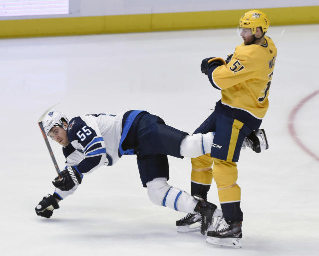 Winnipeg Jets center Mark Scheifele (55) falls to the ice after passing the puck in front of Nashville Predators left wing Austin Watson (51) during the first period of an NHL hockey game Thursday, Jan. 17, 2019, in Nashville, Tenn. (AP Photo/Mark Zaleski)
