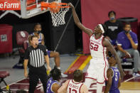 Oklahoma forward Kur Kuath (52) dunks in front of Kansas State guard Selton Miguel (2) and guard Rudi Williams (5) and Oklahoma's Austin Reaves, center, during the first half of an NCAA college basketball game Tuesday, Jan. 19, 2021, in Norman, Okla. (AP Photo/Sue Ogrocki)