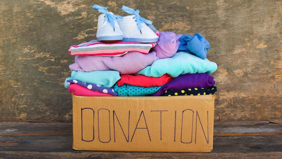 Donation box with children's things on wooden background.