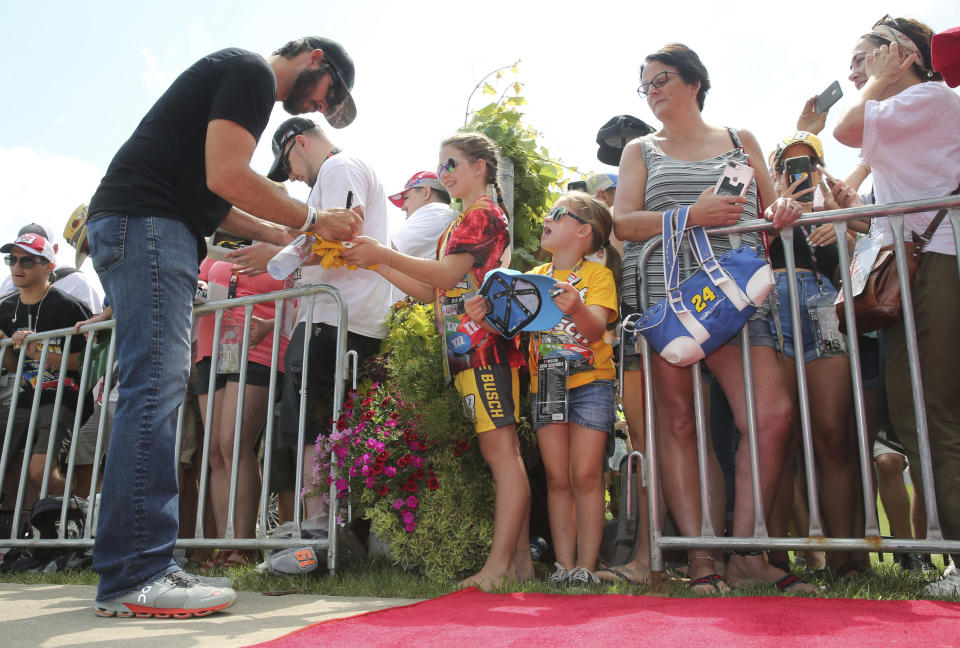 Martin Truex, Jr., signs autographs as he arrives for the driver/crew chief meeting prior to the NASCAR Cup series auto race at Watkins Glen International, Sunday, Aug. 4, 2019, in Watkins Glen, N.Y. (AP Photo/John Munson)