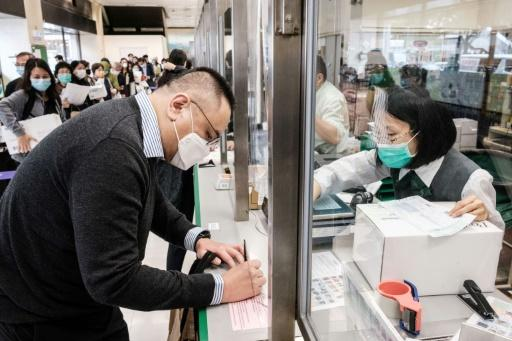 Hong Kongers like Adrian W. Chan (L) are now sending parcels of face masks and other supplies to friends and relatives abroad as the virus spreads