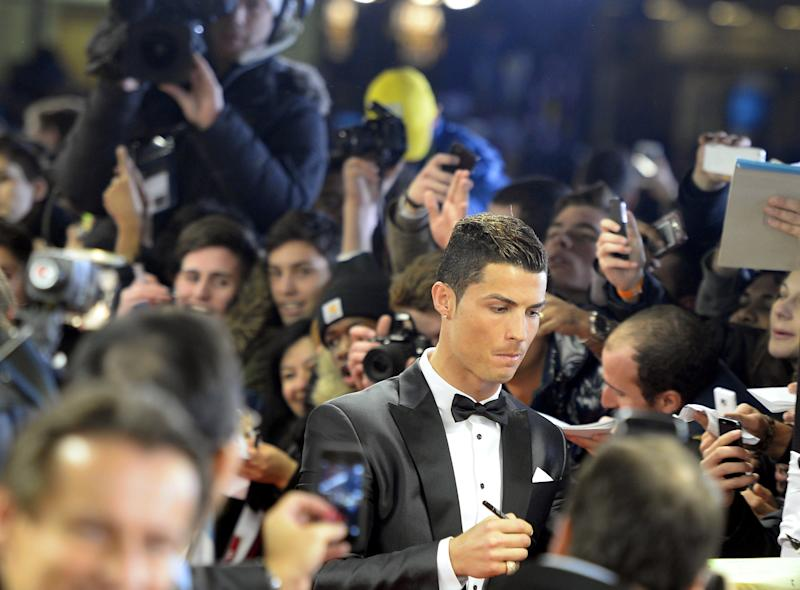Soccer player Cristiano Ronaldo of Portugal signs autographs on the red carpet prior to the FIFA Ballon d'Or 2013 gala held at the Kongresshaus in Zurich, Switzerland, Monday, Jan. 13, 2014. (AP Photo/Keystone,Walter Bieri)