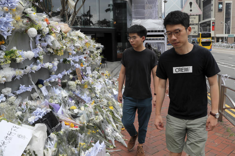 Pro-democracy activist Joshua Wong, left, is accompanied by Nathan Law as they arrive at a makeshift memorial to a pay respect to a protester who fell to his death after hanging a protest banner against an extradition bill in Hong Kong, Monday, June 17, 2019. Wong, a leading figure in Hong Kong's 2014 Umbrella Movement demonstrations, was released from prison on Monday and vowed to soon join the latest round of protests. (AP Photo/Kin Cheung)
