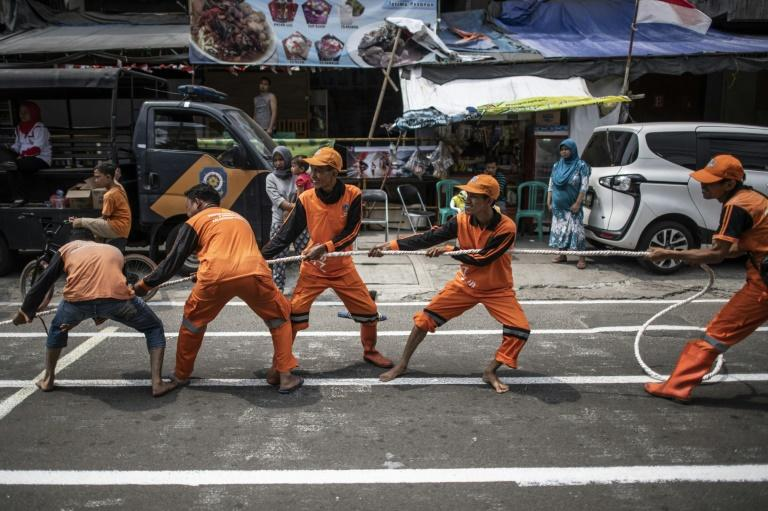 Indonesian workers play a tug-of-war game as part of the 2018 Asian Games in Jakarta