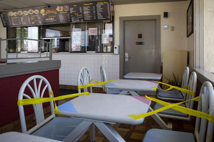 Xs made of yellow tape block off seats at two tables inside a restaurant