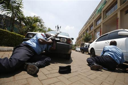 Police take cover outside Westgate shopping centre where gunmen went on a shooting spree in Nairobi September 21, 2013. REUTERS/Goran Tomasevic