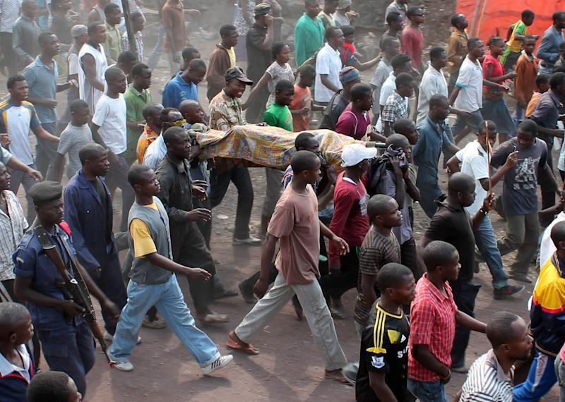 Residents carry the body of a person killed hours earlier when a rocket struck a home, as they take to the streets in protest over recent violence, in Goma, Congo, Saturday, Aug. 24, 2013. Congolese soldiers supported by U.N. forces fought rebels in the country's deteriorating east for hours early Saturday, officials said, while a rocket landed inside the town of Goma. Congo immediately blamed the attacks on neighboring Rwanda, which has long been accused of supporting the eastern Congolese rebel movement known as M23. (AP Photo/Alain Wandimoyi)