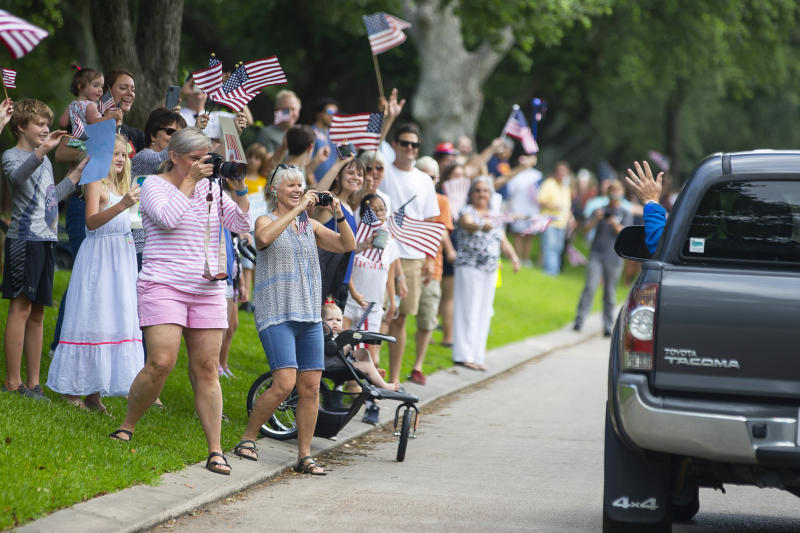 FILE - In this Wednesday, May 20, 2020 file photo, neighbors in Seabrook, Texas wave farewell to astronaut Bob Behnken as he departs for Florida for the upcoming launch of the SpaceX Falcon 9 rocket. Behnken and fellow NASA test pilot Doug Hurley are scheduled to blast off May 27 from the same pad where the space shuttle last soared in 2011. (Mark Mulligan/Houston Chronicle via AP)