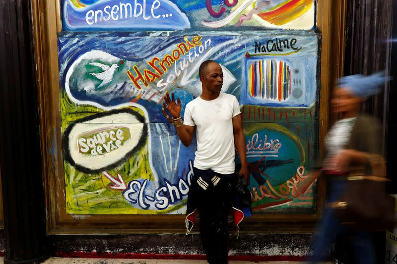Belgian artist Atumesa poses in front of his fresco in the Matonge district of Brussels