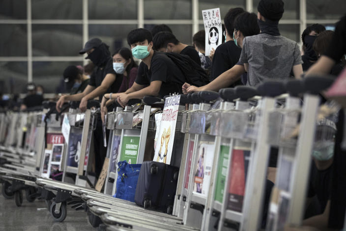Protesters use luggage trolleys to block the departure gates during a demonstration at the Airport in Hong Kong, Tuesday, Aug. 13, 2019. (Photo: Vincent Thian/AP)