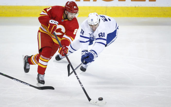 Toronto Maple Leafs' John Tavares, right, checks Calgary Flames' Dominik Simon during the third period of an NHL hockey game, Tuesday, Jan. 26, 2021 in Calgary, Alberta. (Jeff McIntosh/The Canadian Press via AP)