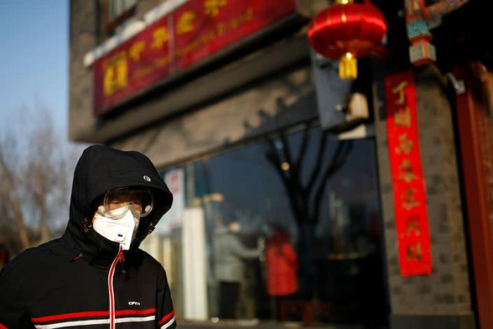 A man wearing a face mask and protective goggles walks along the street as the country is hit by an outbreak of the new coronavirus, in Beijing