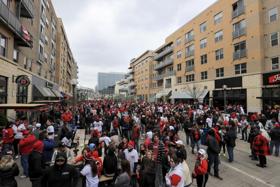 Fans gather outside the ballpark prior to the baseball game between the St. Louis Cardinals and the Cincinnati Reds in Cincinnati, Thursday, April 1, 2021. (AP Photo/Aaron Doster)