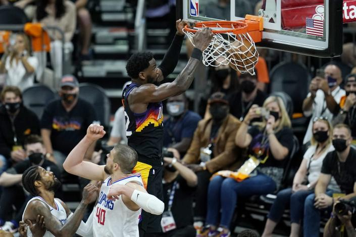 Phoenix Suns center Deandre Ayton, right, dunks as he gets past Los Angeles Clippers center Ivica Zubac (40) and guard Paul George, left, during the second half of Game 1 of the NBA basketball Western Conference finals Sunday, June 20, 2021, in Phoenix. (AP Photo/Ross D. Franklin)