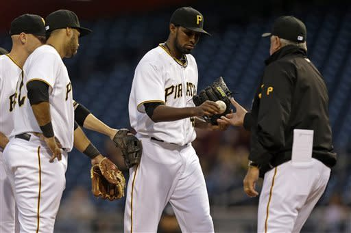 Pittsburgh Pirates starting pitcher James McDonald, center, hands the ball to manager Clint Hurdle, right, as he leaves the game, during the second inning of a baseball game against the St. Louis Cardinals in Pittsburgh Monday, April 15, 2013. At left are Pirates' Pedro Alvarez, front, and Clint Barmes. (AP Photo/Gene J. Puskar)