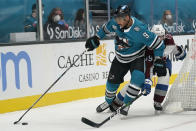 San Jose Sharks left wing Evander Kane (9) reaches for the puck in front of Colorado Avalanche defenseman Samuel Girard during the second period of an NHL hockey game in San Jose, Calif., Monday, March 1, 2021. (AP Photo/Jeff Chiu)