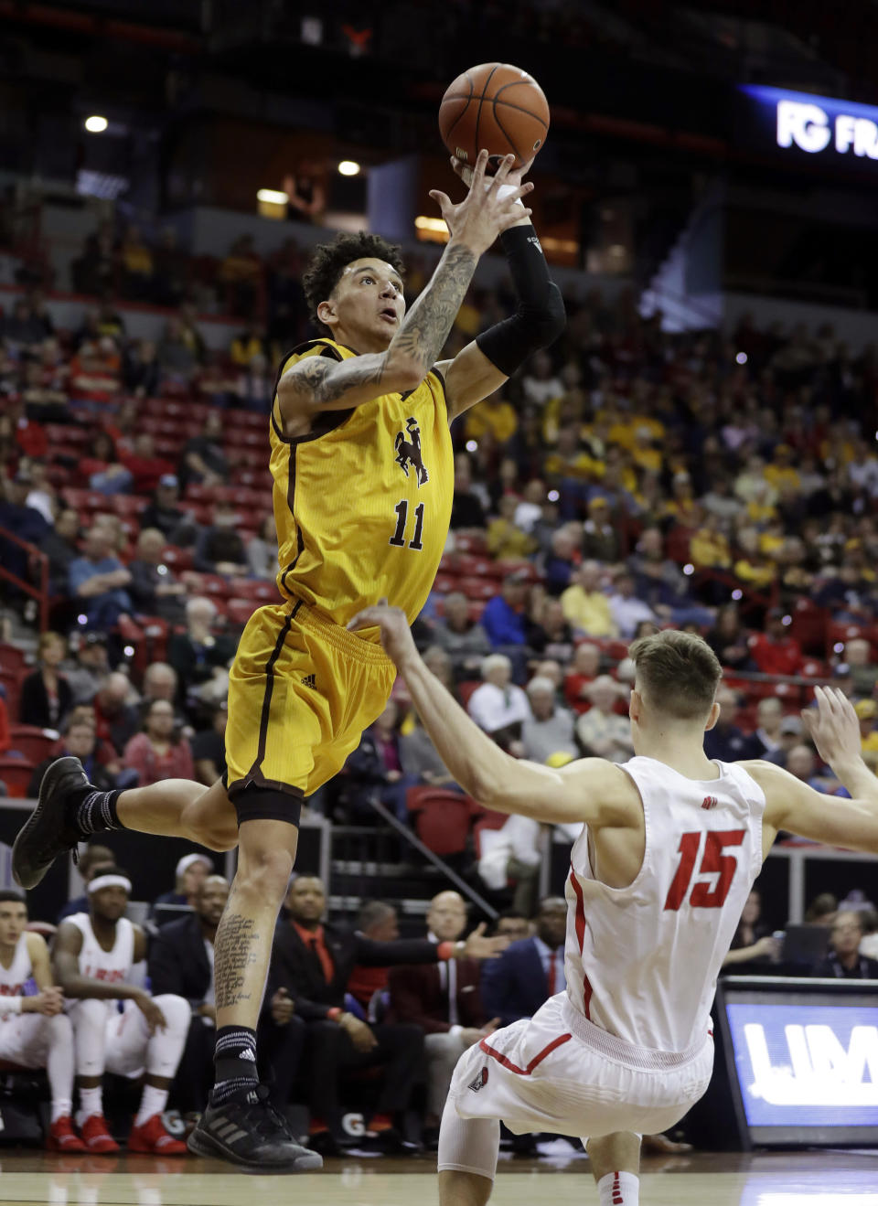 Wyoming's Trace Young shoots over New Mexico's Trey Porter during the first half of an NCAA college basketball game in the Mountain West Conference tournament, Wednesday, March 13, 2019, in Las Vegas. (AP Photo/Isaac Brekken)
