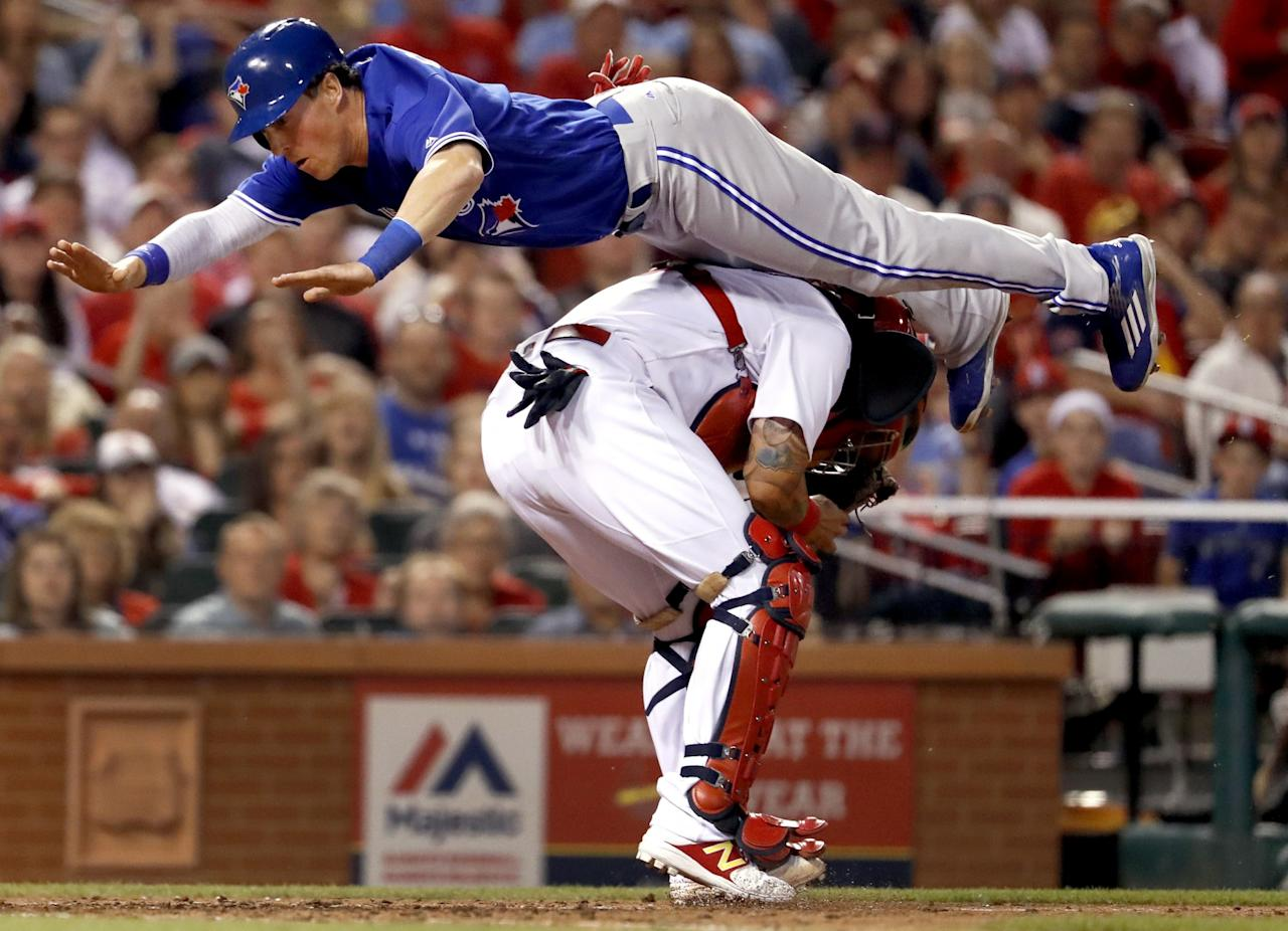 <p>Toronto Blue Jays' Chris Coghlan leaps over St. Louis Cardinals catcher Yadier Molina to score during the seventh inning of a baseball game Tuesday, April 25, 2017, in St. Louis. (AP Photo/Jeff Roberson) </p>
