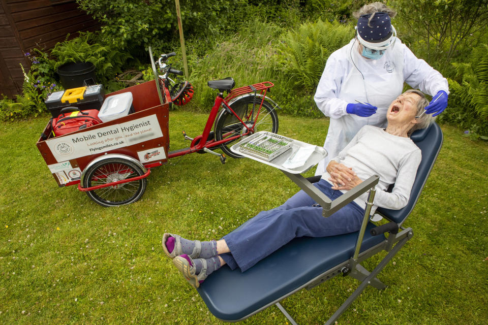 Fiona Perry works on 89-year-old Jean Temple in her garden. (SWNS)