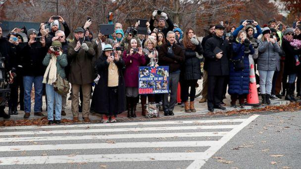 PHOTO: People line the street as the hearse carrying the flag-draped casket of former President George H.W. Bush heads to a State Funeral at the National Cathedral, Dec. 5, 2018, in Washington. (Alex Brandon/Pool via Reuters)