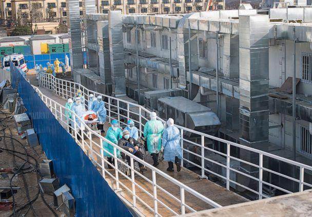 PHOTO: In this photo released by China's Xinhua News Agency, medical workers in protective suits help transfer the first group of patients into the newly-completed Huoshenshan temporary field hospital in Wuhan in central China's Hubei province. (Xiao Yijiu/Xinhua via AP)