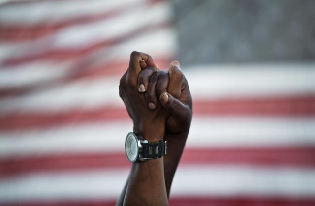 <p>People join hands against the backdrop of an American flag as thousands of marchers meet in the middle of Charleston's main bridge in a show of unity after nine black church parishioners were gunned down during a Bible study, June 21, 2015, in Charleston, S.C. (AP Photo/David Goldman) </p>