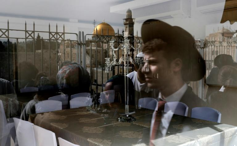 A picture taken through the window of a restaurant shows a reflection of Jews taking part in the Passover priestly blessing at Jerusalem's Western Wall on April 13, 2017, with the Dome of the Rock seen in the background