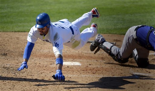 Los Angeles Dodgers' Matt Kemp, left, falls after being tagged out at home by Colorado Rockies catcher Jordan Pacheco as he tried to score on a single by Hanley Ramirez during the fifth inning of their baseball game, Sunday, Sept. 30, 2012, in Los Angeles. (AP Photo/Mark J. Terrill)