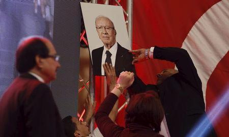 A man attaches a picture of  President Beji Caid Essebsi's  during a meeting from  Mohsen Marzouk in Tunis