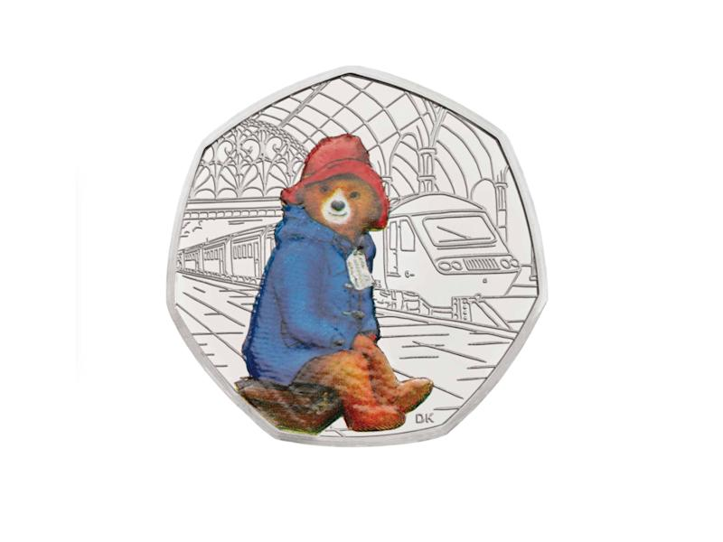 The adventurous bear is waiting patiently for his train on this commemorative coinThe Royal Mint