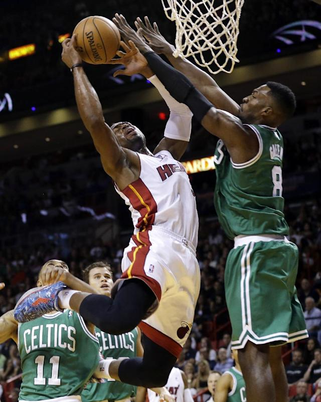 Miami Heat's Dwyane Wade, left, is fouled by Boston Celtics' Jeff Green (8) during the first half of an NBA basketball game Saturday, Nov. 9, 2013, in Miami. (AP Photo/Lynne Sladky)