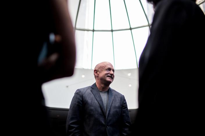 Image: Mark Kelly speaks with guests at a summit in Atlanta in 2014. (Branden Camp / AP file)