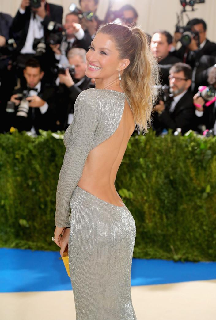 gisele bundchen wearing backless silver gown at the met gala in 2017