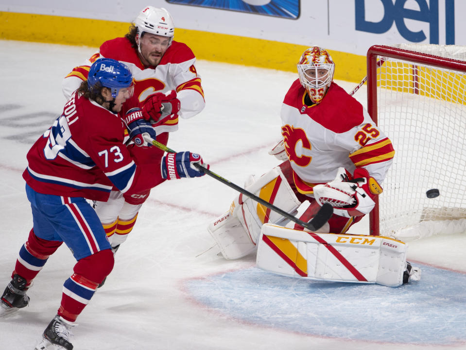 Montreal Canadiens' Tyler Toffoli (73) tries to knock in a loose puck as Calgary Flames goaltender Jacob Markstrom (25) and Flames' Rasmus Andersson (4) look on during the second period of an NHL hockey game Wednesday, April 14, 2021 in Montreal. (Ryan Remiorz/Canadian Press via AP)