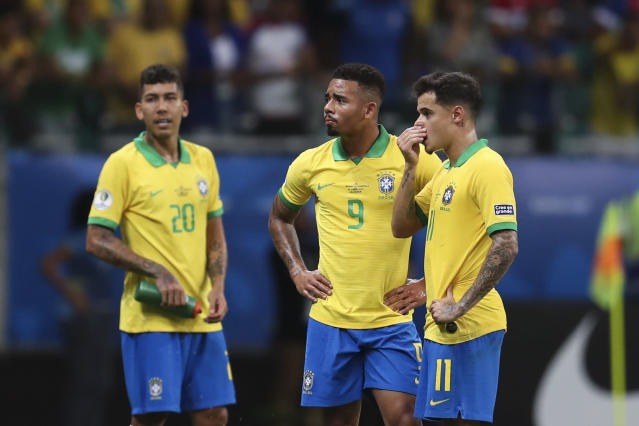 Brazil's Gabriel Jesus, center, waits for the referee to decide on his goal with teammates Brazil's Roberto Firmino, left, and Brazil's Philippe Coutinho, right, during a Copa America Group A soccer match at the Arena Fonte Nova in Salvador, Brazil, Tuesday, June 18, 2019. Referee Julio Bascunan, not in picture, annulled Gabriel Jesus' goal due to an offside position. (AP Photo/Natacha Pisarenko)