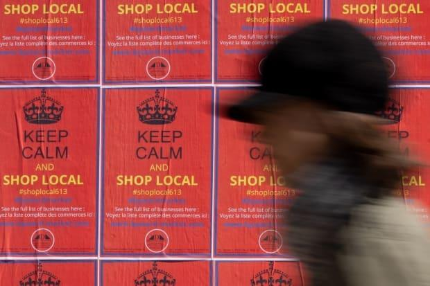 A pedestrian passes a wall of posters asking people to support business in Ottawa's ByWard Market on April 1, 2021. (Andrew Lee/CBC - image credit)