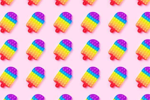 Pattern with rainbow pop it anti-stress toy isolated on pink background. Close-up. (Photo: Evgeniia Siiankovskaia via Getty Images)