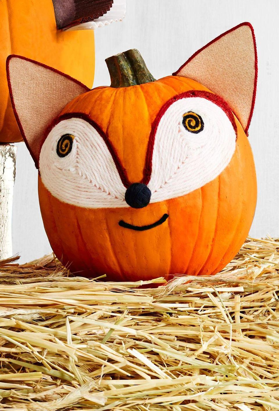 """<p>You don't need to be sly as a fox recreate this friendly fur critter. <br></p><p><strong>Make the pumpkin:</strong> Using this image as a guide, outline the face silhouette with pencil first. For the pupils, hot-glue black and orange yarn in a spiral pattern directly onto the pumpkin. Hot-glue a continuous piece of white yarn in a teardop pattern until the space is fully filled. Outline the eyes with rust yarn, then add a black yarn mouth and pom-pom nose. For ears, glue felt on <a href=""""https://www.amazon.com/Chipboard-Standard-Cardboard-Packaging-Paper/dp/B01CQA0UMO/?tag=syn-yahoo-20&ascsubtag=%5Bartid%7C10050.g.28437255%5Bsrc%7Cyahoo-us"""" rel=""""nofollow noopener"""" target=""""_blank"""" data-ylk=""""slk:cover-weight paper backing"""" class=""""link rapid-noclick-resp"""">cover-weight paper backing</a>. Cut into triangles, trim with rust yarn, and glue to the top of the pumpkin. </p>"""