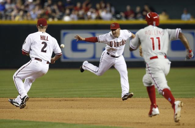 Arizona Diamondbacks' Cliff Pennington, middle, flips the ball to Aaron Hill (2) to get a force out on Philadelphia Phillies' Jimmy Rollins (11) at second base during the fourth inning of a baseball game on Friday, April 25, 2014, in Phoenix. Chase Utley was safe at first. (AP Photo/Ross D. Franklin)