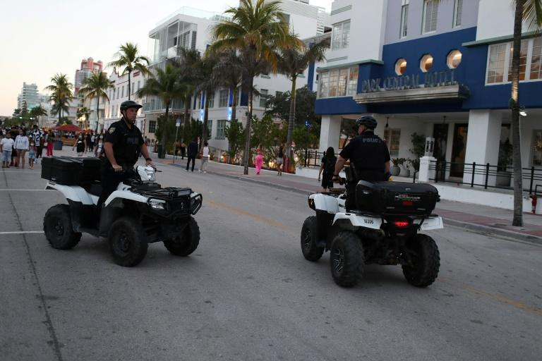Miami Beach police officers patrol along the city's Ocean Drive on March 21, 2021