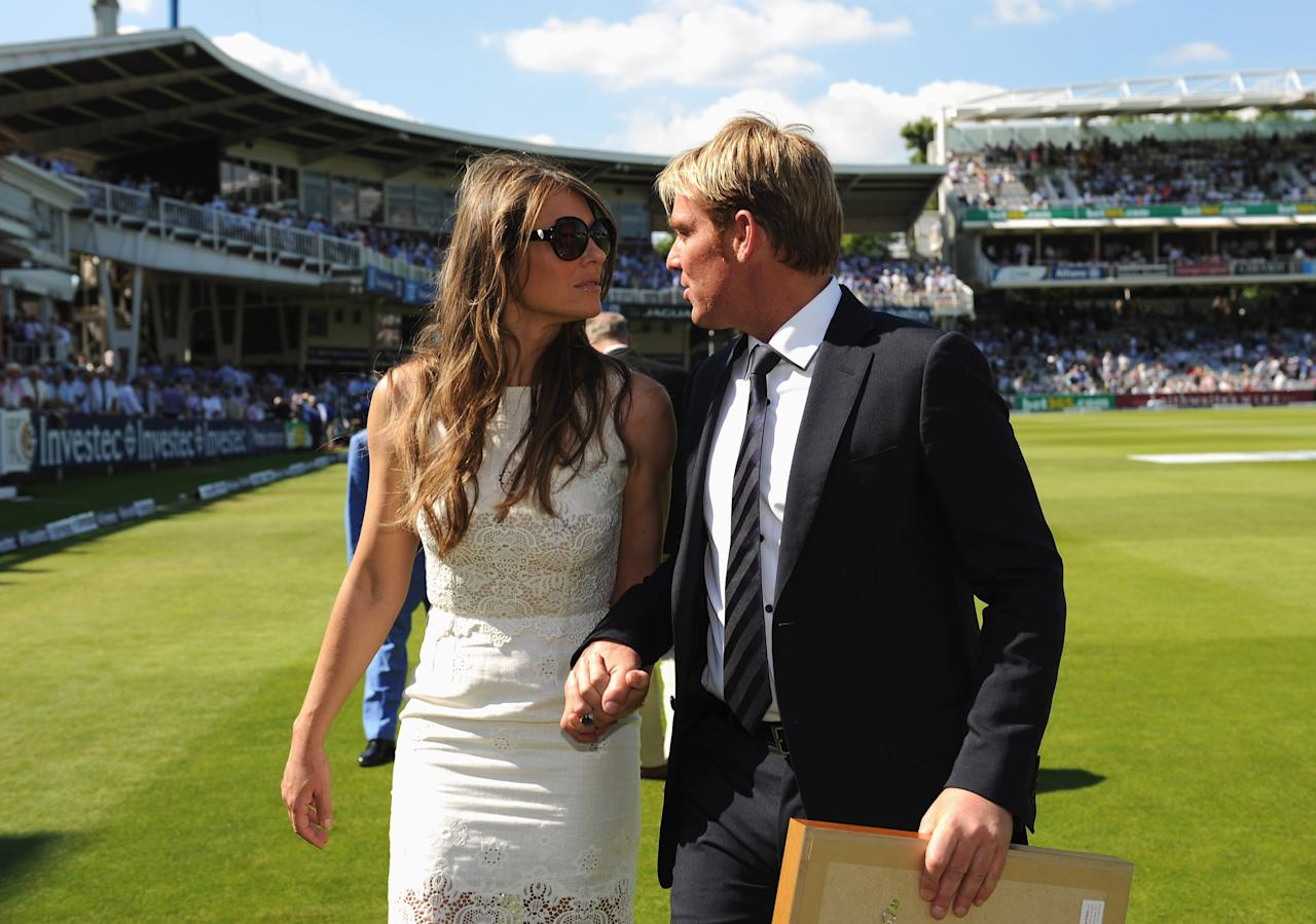 LONDON, ENGLAND - JULY 19: Shane Warne of Australia walks with Elizabeth Hurley after being inducted into the ICC Hall of Fame during day two of the 2nd Investec Ashes Test match between England and Australia at Lord's Cricket Ground on July 19, 2013 in London, England. (Photo by Gareth Copley/Getty Images)
