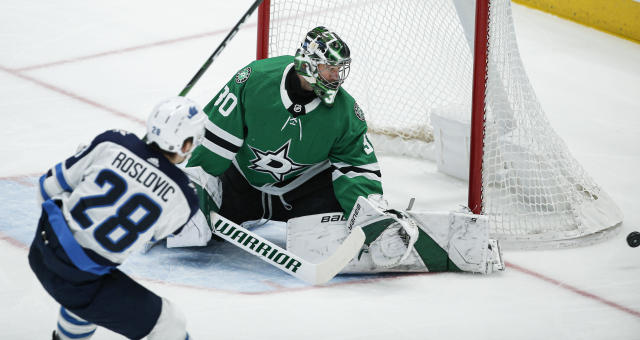 Dallas Stars goaltender Ben Bishop (30) deflects a shot from Winnipeg Jets forward Jack Roslovic (28) during the first period an NHL hockey game Thursday, Dec. 5, 2019, in Dallas. Dallas won 3-2 in overtime. (AP Photo/Brandon Wade)