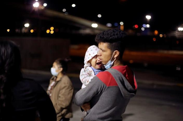 Stephanie, 10 months old, cries as she is carried by her father Manuel de Jesus Martinez, an asylum-seeking migrant from Honduras, who was airlifted from Brownsville to El Paso, Texas, and deported from the U.S. with her, in Ciudad Juarez