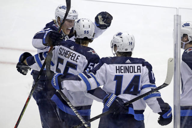Winnipeg Jets' Ville Heinola (14) celebrates his goal with Mark Scheifele (55) and Patrik Laine (29) during the first period of an NHL hockey game against the Pittsburgh Penguins in Pittsburgh, Tuesday, Oct. 8, 2019. (AP Photo/Gene J. Puskar)