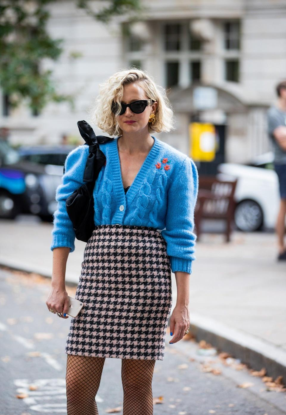 """This cardigan and houndstooth skirt combo is one we're bookmarking for our <a href=""""https://www.refinery29.com/en-gb/autumn-transitional-office-wear-clothing"""" rel=""""nofollow noopener"""" target=""""_blank"""" data-ylk=""""slk:back-to-work wardrobe"""" class=""""link rapid-noclick-resp"""">back-to-work wardrobe</a>. <span class=""""copyright"""">Photo Courtesy Of Christian Vierig/Getty Images.</span>"""