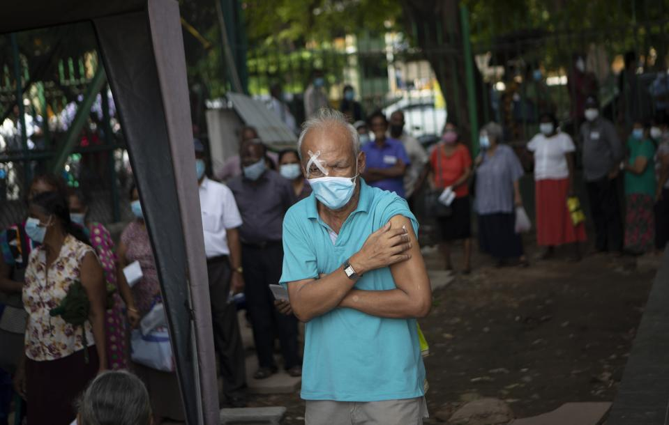 An elderly man holds his arm after receiving a dose of Pfizer COVID-19 vaccine at a vaccination site in Colombo, Sri Lanka, Wednesday, July 7, 2021. Sri Lankan health authorities on Wednesday began rolling out doses of the Pfizer vaccine for those who have received only the first dose of the AstraZeneca vaccine. Health officials were compelled to use Pfizer as the second dose due to a shortage of AstraZeneca vaccines. (AP Photo/Eranga Jayawardena)