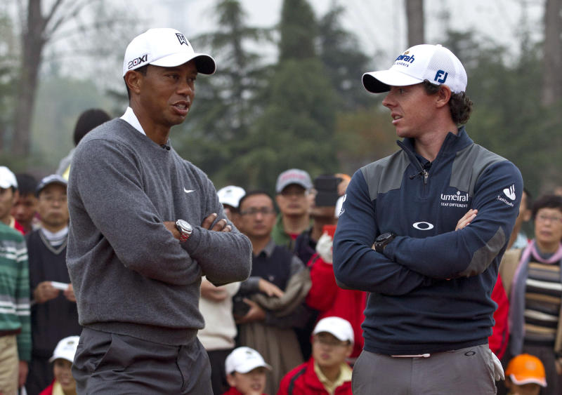 FILE - In this Oct. 29, 2012 photo, Tiger Woods, left, and Rory McIlroy, right, wait for the award ceremony after their 18-hole medal-match at the Lake Jinsha Golf Club in Zhengzhou, in central China's Henan province. The world's two top golfers are meeting more and more often on the course, but neither No. 1-ranked Rory McIlroy or Tiger Woods are ready to call it a rivalry. The pair, set to meet at the Abu Dhabi Golf Championship, starting from Jan. 17, 2013,  have established a blossoming relationship since playing together for the first three rounds of last year's tournament and have expressed a mutual respect for one another's game.  (AP Photo/Alexander F. Yuan File)