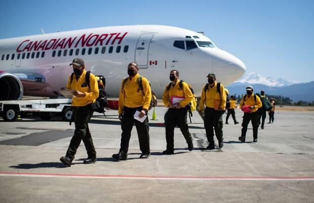 Firefighters from Mexico walk across the tarmac after arriving on a charter flight in Abbotsford, B.C., on Saturday to help the province deal with hundreds of wildfires. They will undergo rapid COVID-19 testing and then be deployed to the B.C. Interior. (Darryl Dyck/The Canadian Press - image credit)