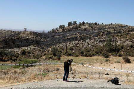 A cameraman films next to a slope where a missile struck in  Tashkent (also known as Vouno), in northern Cyprus